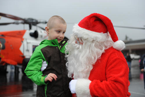 Braydan White (left), 5-year-old Seaside, Ore., community member and avid Christmas fan, visits with Santa in the Seaside Outlet Mall parking lot, November 17, 2012. A Coast Guard MH-60 Jayhawk helicopter crew from Sector Columbia River's Air Station Astoria transported Santa to the mall to help spread the word about a Toys for Tots campaign being held this holiday season along Oregon's North Coast and Southwestern Washington state. U.S. Coast Guard photo by Petty Officer 3rd Class Nate Littlejohn