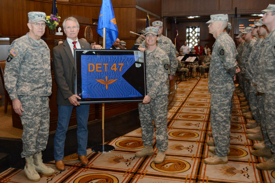 Oregon Governor John Kitzhaber accepts a framed unit guidon flag from Maj. Sarah Fritts (right), commander of Detachment 47, 2-641 Aviation, as Maj. Gen. Raymond F. Rees (left), Adjutant General, Oregon, looks on during the mobilization ceremony for two aviation units in the Senate Chamber at the State Capitol in Salem, Ore., Feb. 21. The governor keeps framed guidon&#039;s of deployed Oregon Army National Guard units until they return home to Oregon. Five Soldiers with Detachment 47, 2-641 Aviation, will deploy to Afghanistan in support of the Communications Electronic Attack with Surveillance and Reconnaissance (CEASAR) mission. (Photo by Staff Sgt. April Davis, Oregon Military Department Public Affairs)